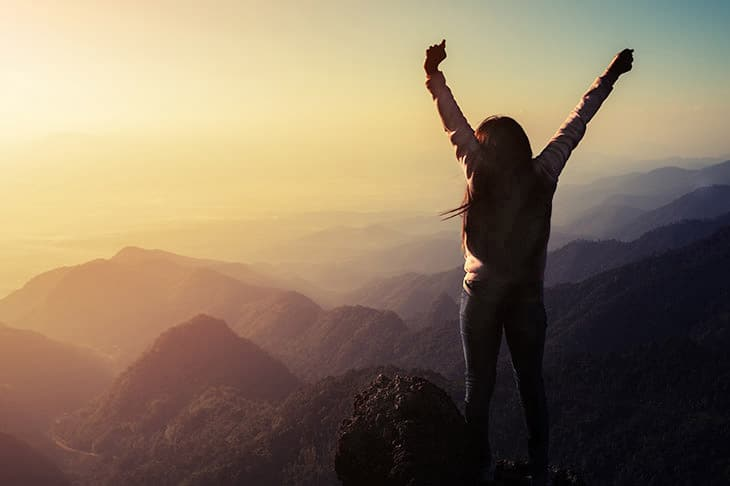 A lady is cheering her victory at overcoming under performance anxiety the top of the mountain